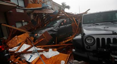 A storm chaser climbs into his vehicle during the eye of Hurricane Michael to retrieve equipment after a hotel canopy collapsed in Panama City Beach, Florida.