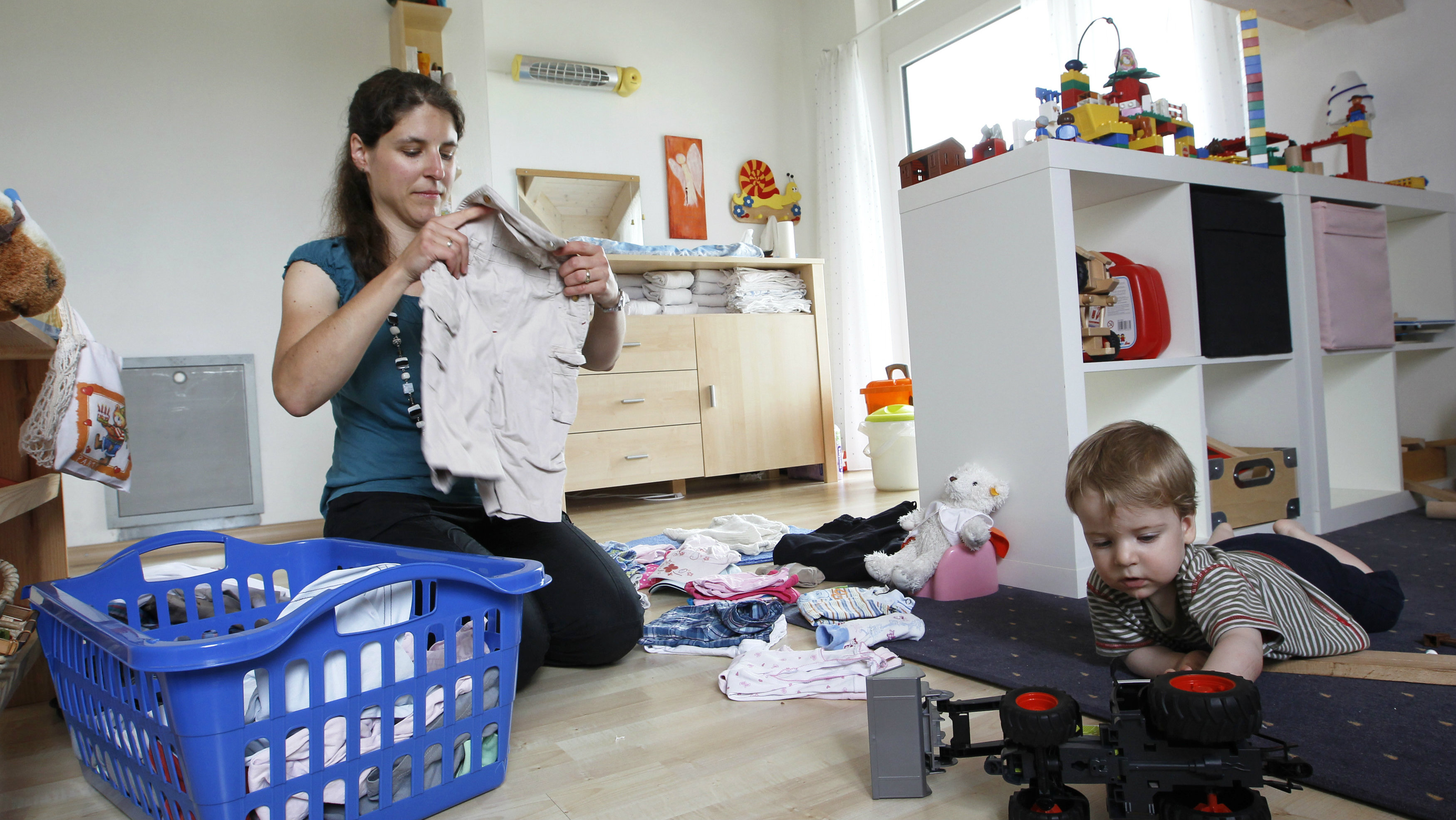 A woman folds clothes in the playroom next to her son.