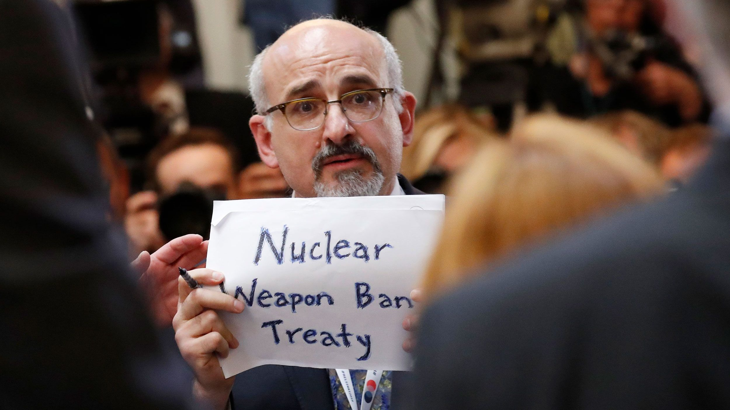A man holds a sign reading 'Nuclear Weapon Ban Treaty' at Trump and Putin's meeting in Finland in July 2018.
