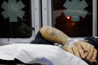 """A 41-year-old man found unconscious after overdosing on opioids in the driver's seat of a car, with the engine running and the transmission in drive, puts his hands over his head in the back of a Cataldo Ambulance at a gas station in the Boston suburb of Malden, Massachusetts, December 2, 2017. A used syringe was found in the car with the victim, who was revived with 10mg of naloxone. REUTERS/Brian Snyder SEARCH """"SNYDER OPIOIDS"""" FOR THIS STORY. SEARCH """"WIDER IMAGE"""" FOR ALL STORIES. - RC13F461C890"""
