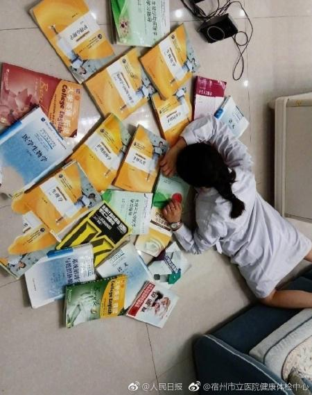 A student laying on the ground with books around her as a way to participate in the flaunt wealth challenge.