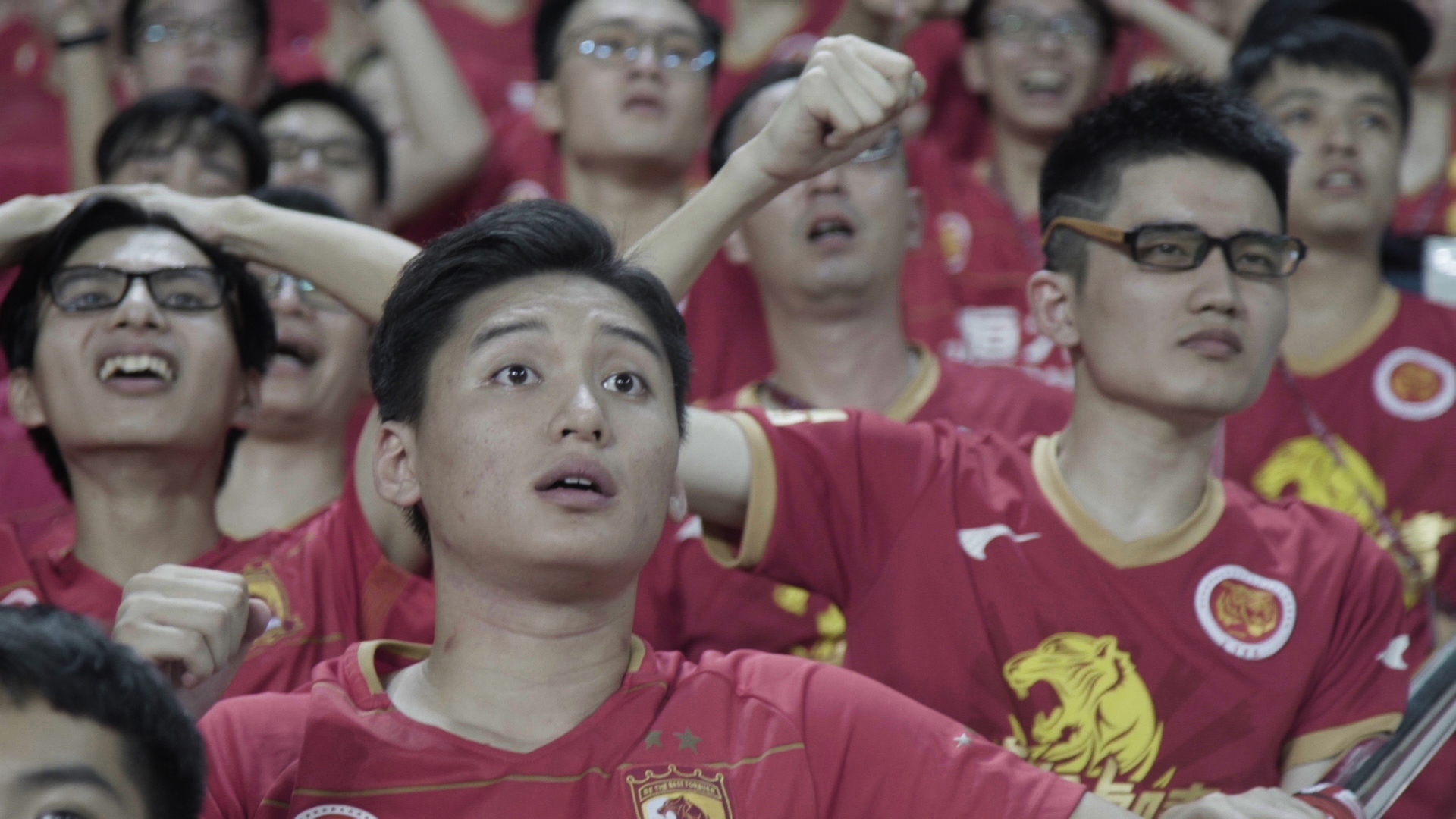 Fans of Guangzhou Evergrande Taobao Football Club cheer on their team at a football match.