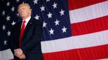 U.S. President Donald Trump stands in front of a U.S. flag