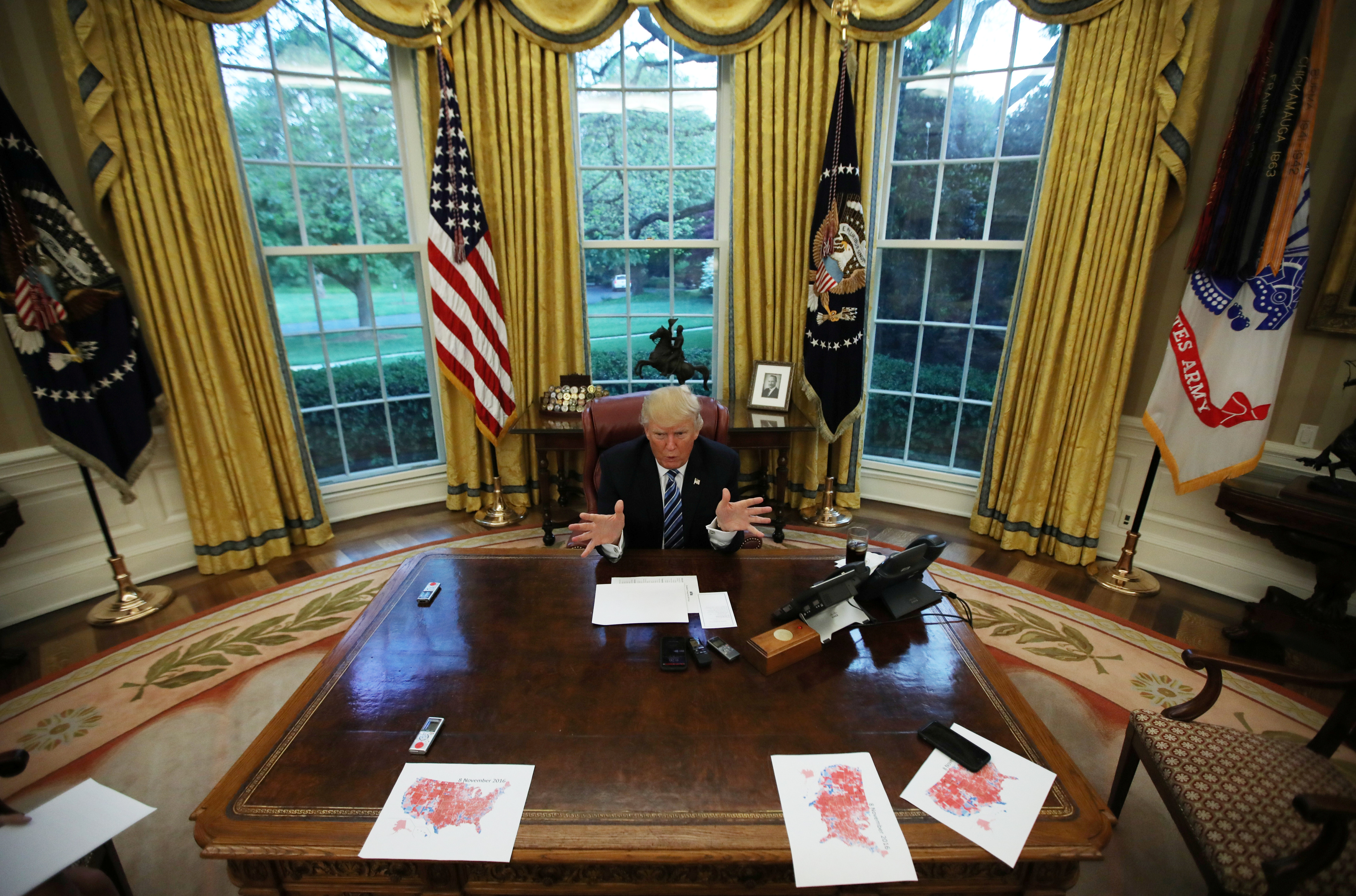 U.S. President Donald Trump speaks during an interview with Reuters in the Oval Office of the White House in Washington, U.S., April 27, 2017. On his desk are maps of the United States that intentionally misplace Alaska and Hawaii so the states can be viewed in detail.