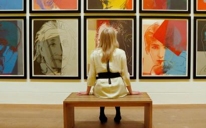 """Gallery employee Maddy Adeane poses with Andy Warhol's """"Ten Portraits of Jews of the Twentieth Century"""""""