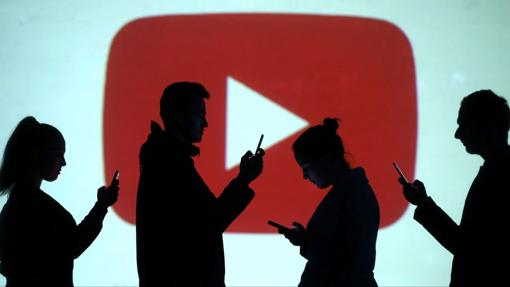 Silhouettes of mobile users are seen next to a screen projection of Youtube logo in this picture illustration taken March 28, 2018.