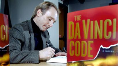 "**FILE**Author Dan Brown is seen thorugh copies of his book during a book signing at the Exeter Public Library in Exeter, N.H. on May 13, 2003. Nearly three years after it was first published, Brown's ""The Da Vinci Code"" has more than 25 million copies in print worldwide, inspired dozens of parodies and critiques and increased interest in religious thrillers, art history, Gnostic texts and speculations about the life of Jesus. (AP Photo/Tim Boyd)"