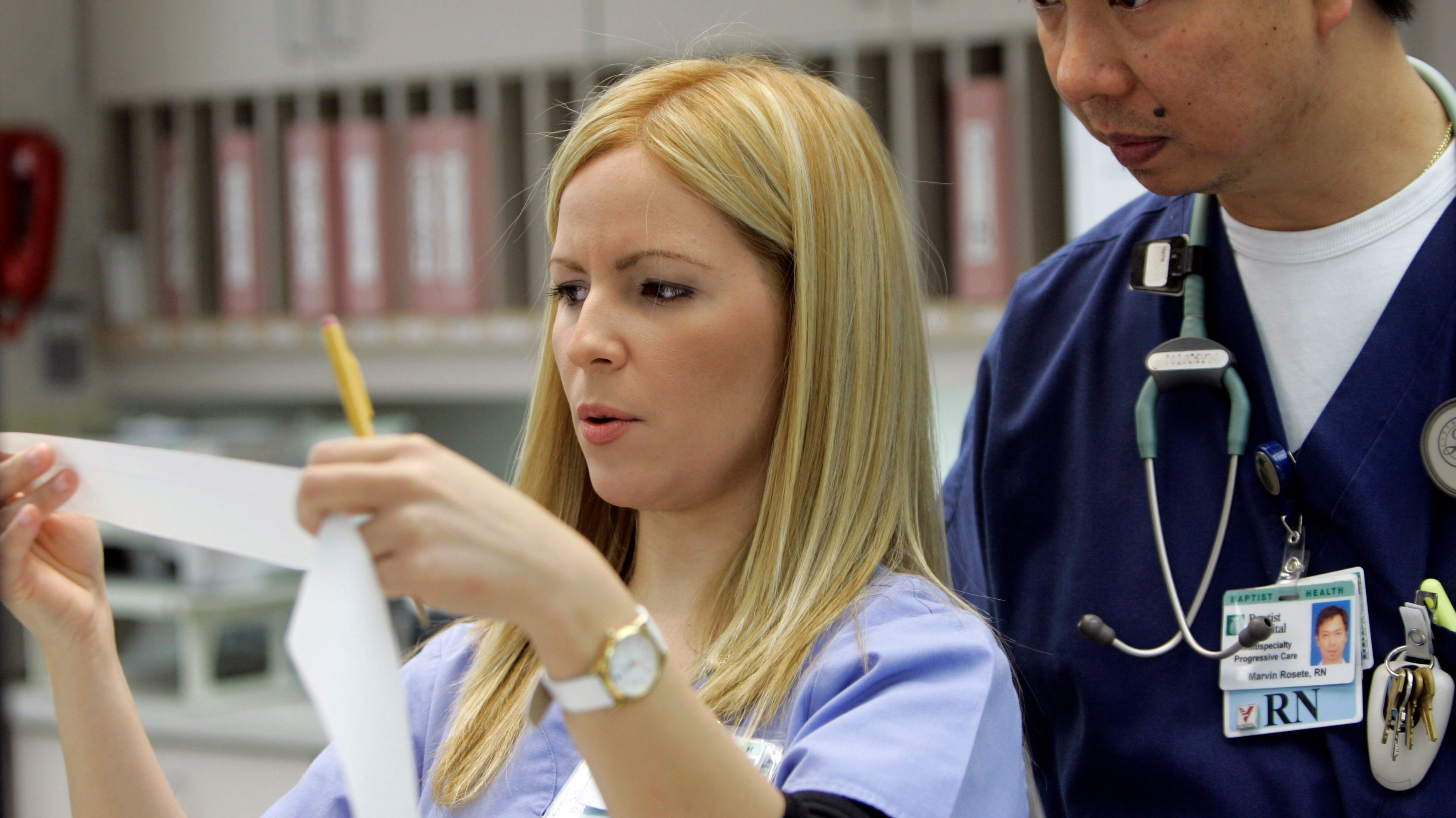 A nurse reading an electrocardiogram result.