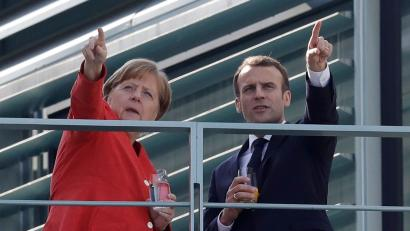 French President Emmanuel Macron, right, and German Chancellor Angela Merkel take a break on a balcony of Merkel's office.