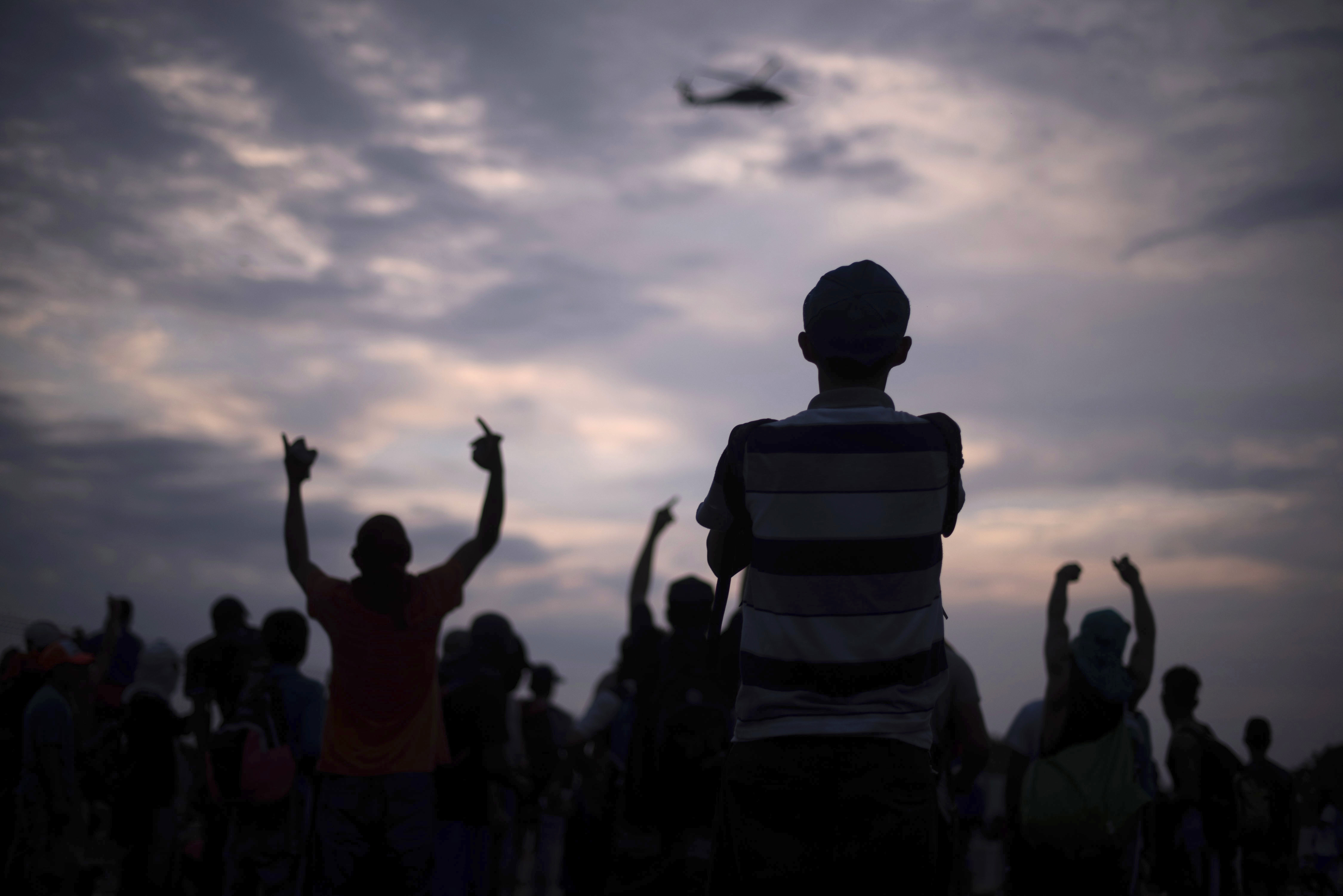 Central American migrants watch as a Mexican Federal Police helicopter flies over the border bridge connecting Guatemala and Mexico in Tecun Uman, Guatemala, Sunday, Oct. 28, 2018.