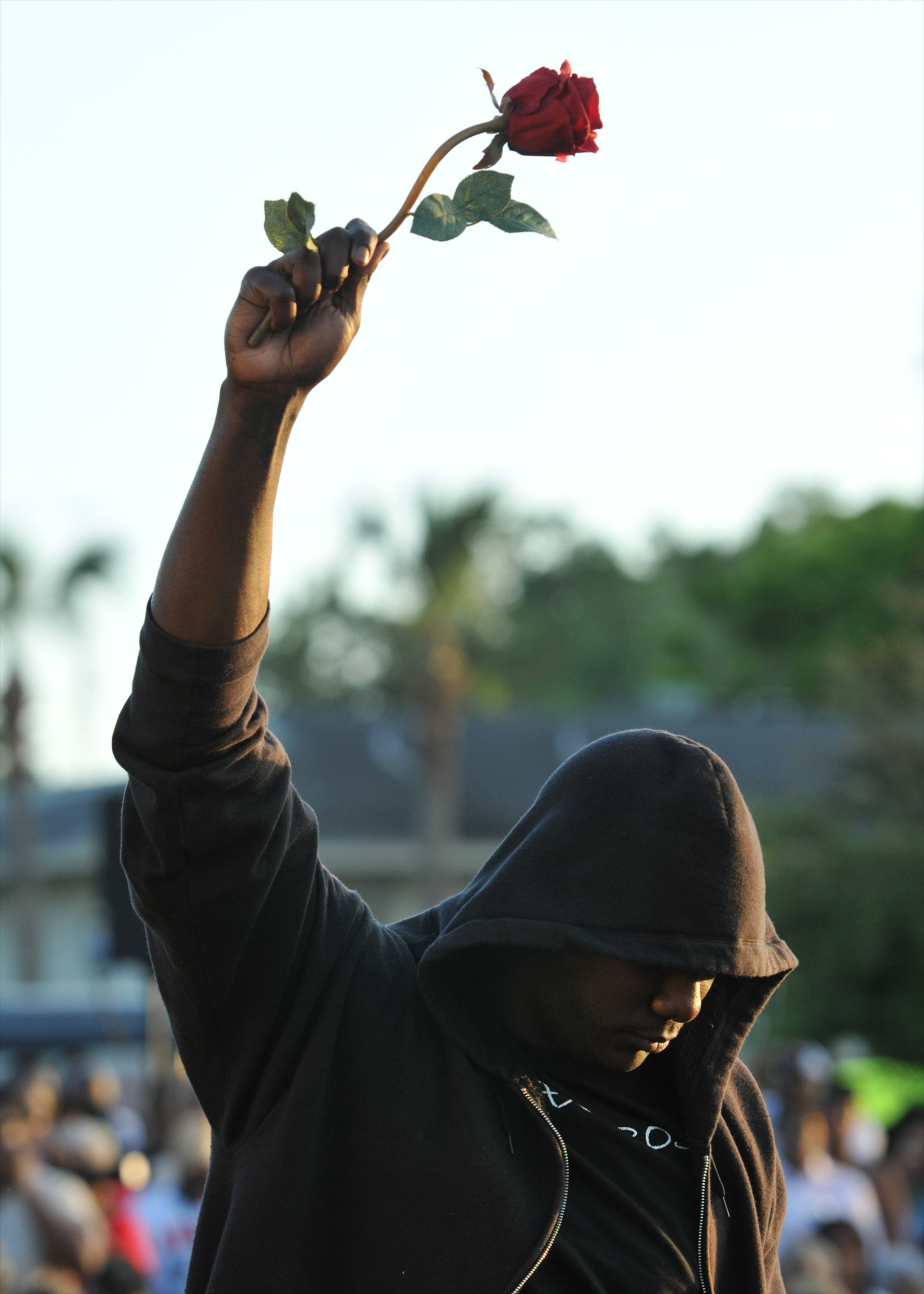 FILE - In this March 22, 2012 file photo James Gilchrist of Orlando, Fla., wearing a hoodie and holding a rose, attends a rally for Trayvon Martin in Sanford, Fla. Martin was shot by George Zimmerman, who claimed self-defense, as he patrolled a gated community in Florida. Though he was not a sworn police officer, his case raised some of the same questions in the wake of the killing of 18-year old Michael Brown in Missouri about the role race might pay in the killings of young black men by people in positions of authority. (AP Photo/Roberto Gonzalez, File)