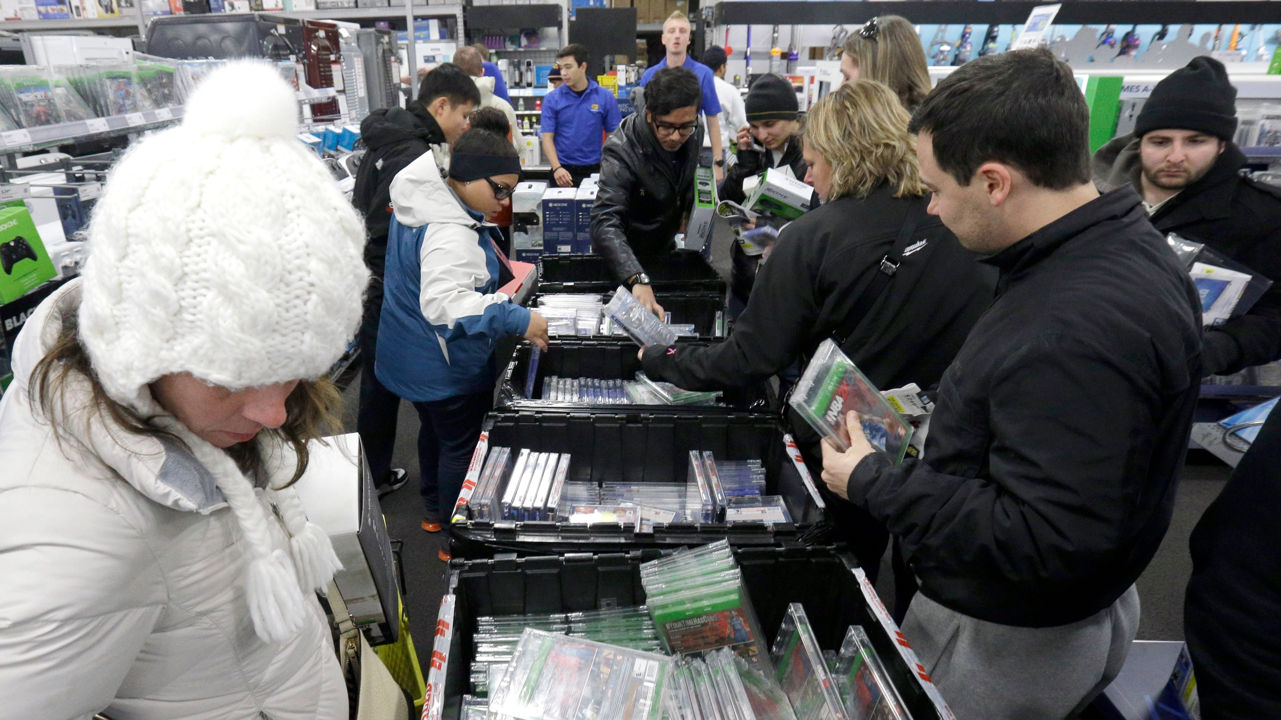 Shoppers sift through video games at a Best Buy on Thursday, Nov. 27, 2014, in Northbrook, Ill. Early-bird shoppers headed to stores on Thanksgiving in what's becoming a new holiday tradition. (AP Photo/Nam Y. Huh)