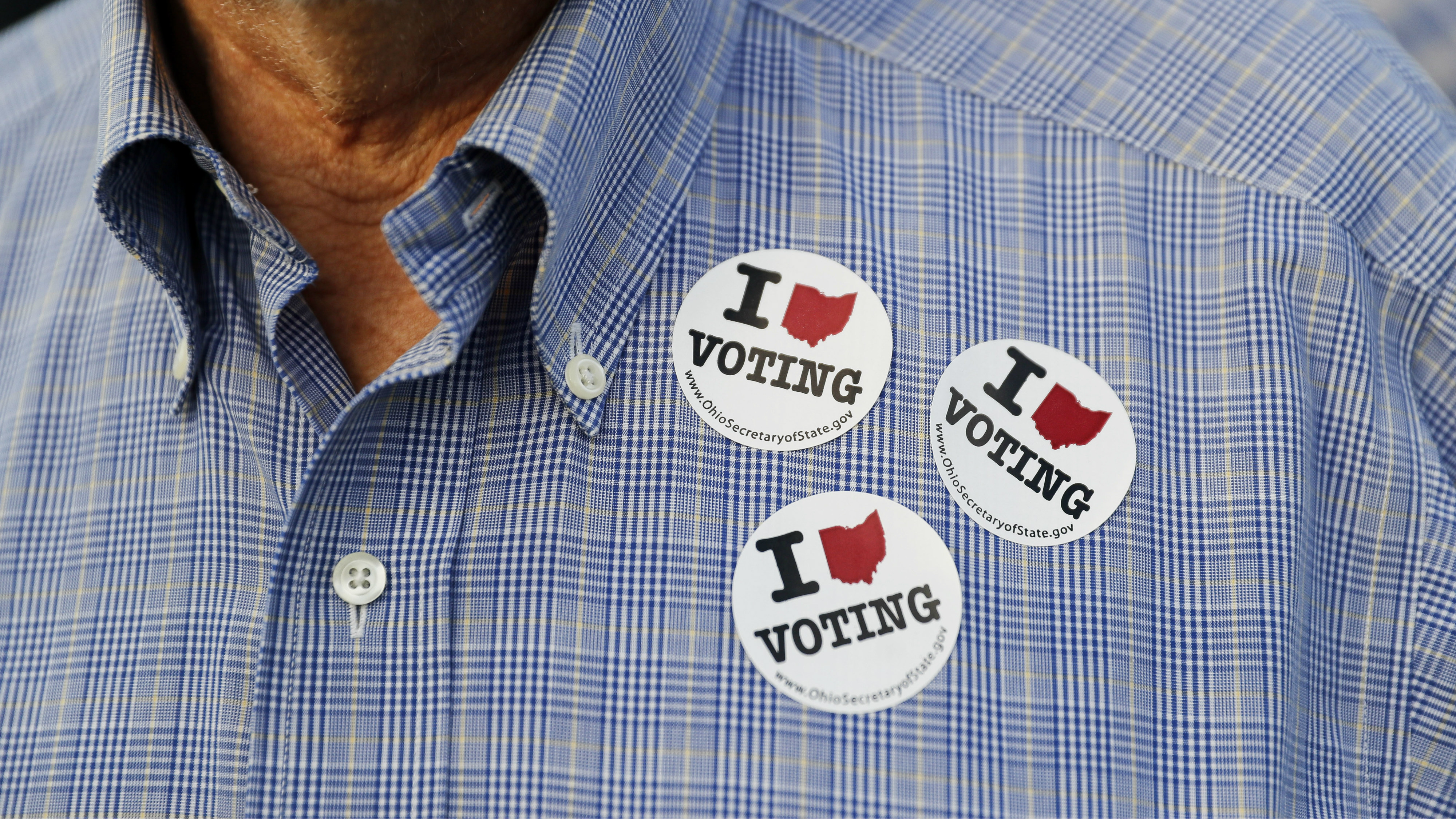 A person with voting stickers on their shirt.