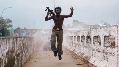 MONROVIA, LIBERIA - JULY 20: Joseph Duo, a Liberian militia commander loyal to the government, exults after firing a rocket-propelled grenade at rebel forces at a key strategic bridge July 20, 2003 in Monrovia, Liberia. Government forces succeeded in forcing back rebel forces in fierce fighting on the edge of Monrovia's city center.