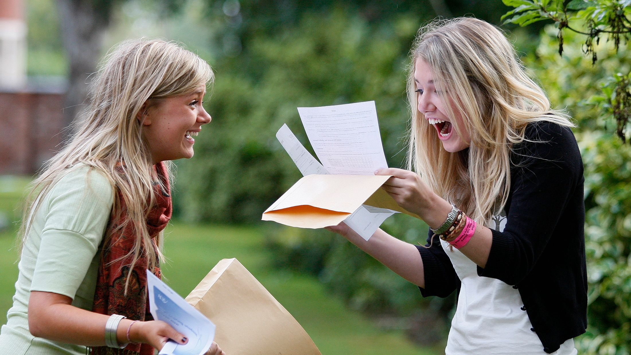 Pupils Alice Wright (L) and Rebecca Pinder from Withington Girls School in Manchester, northern England, react after receiving their A-level exam results, August 16, 2007. Alice received five A grades, Rebecca received four grade A's and an AA merit. More than a quarter of A-level papers received the top grade this year, the highest percentage ever, according to figures released on Thursday. REUTERS/Phil Noble (BRITAIN) - GM1DVYBUMYAA