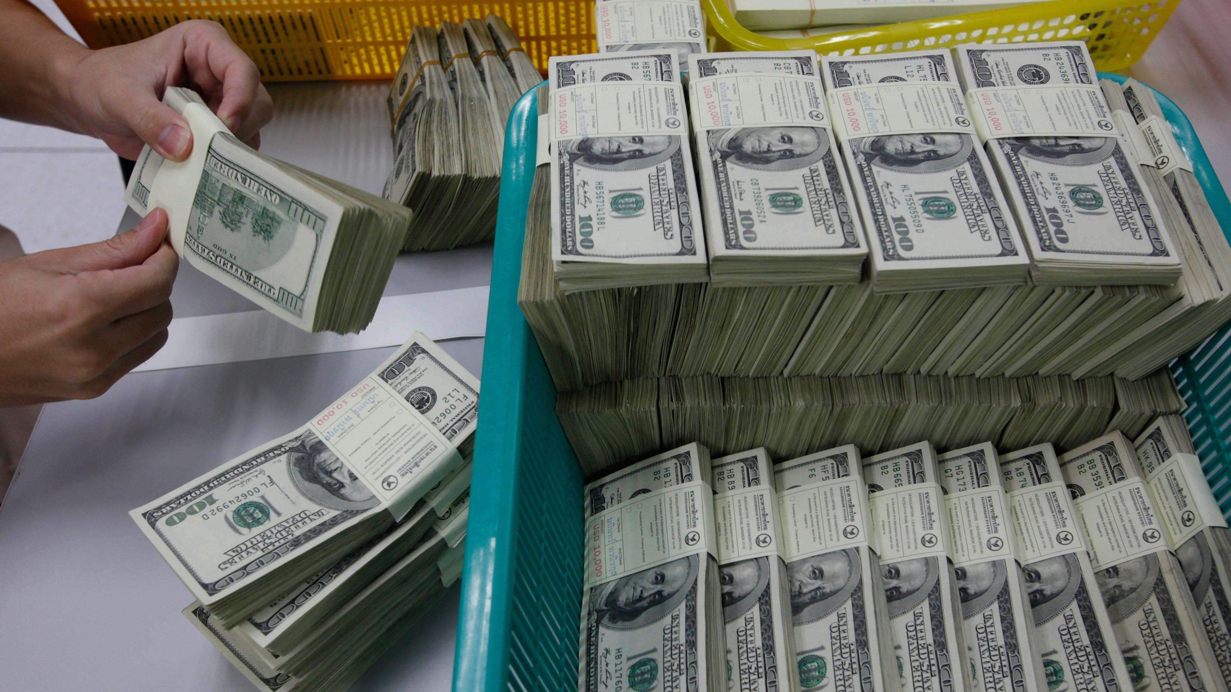 A bank employee counts U.S. hundred dollar bills at Kasikornbank in Bangkok