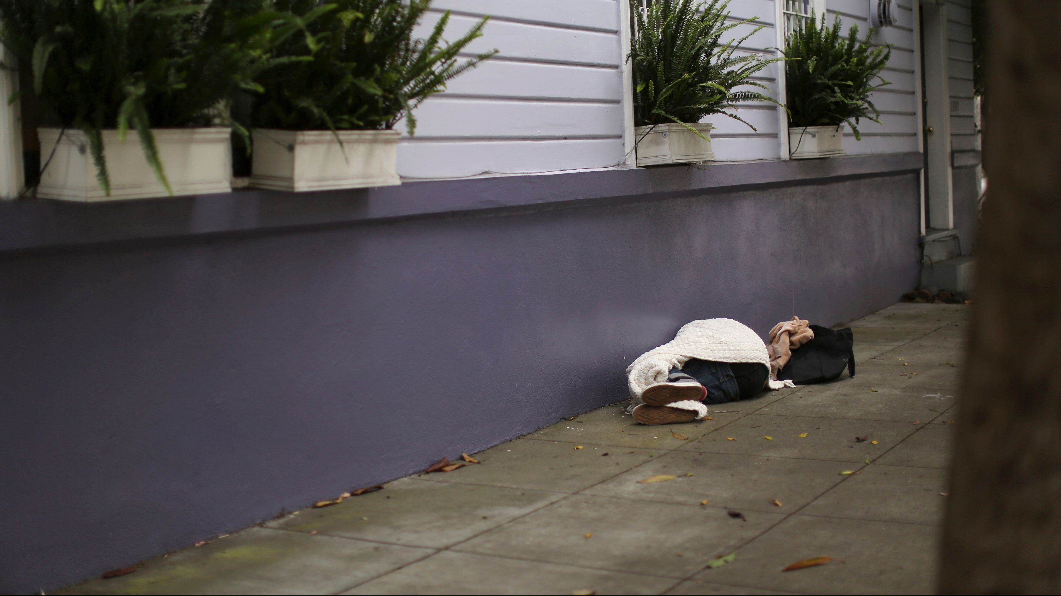 A person sleeps on a sidewalk in the Haight Ashbury neighborhood in San Francisco, California July 17, 2014. The median price for a single-family home or condominium rose to $1 million in June, according to a report released by DataQuick.