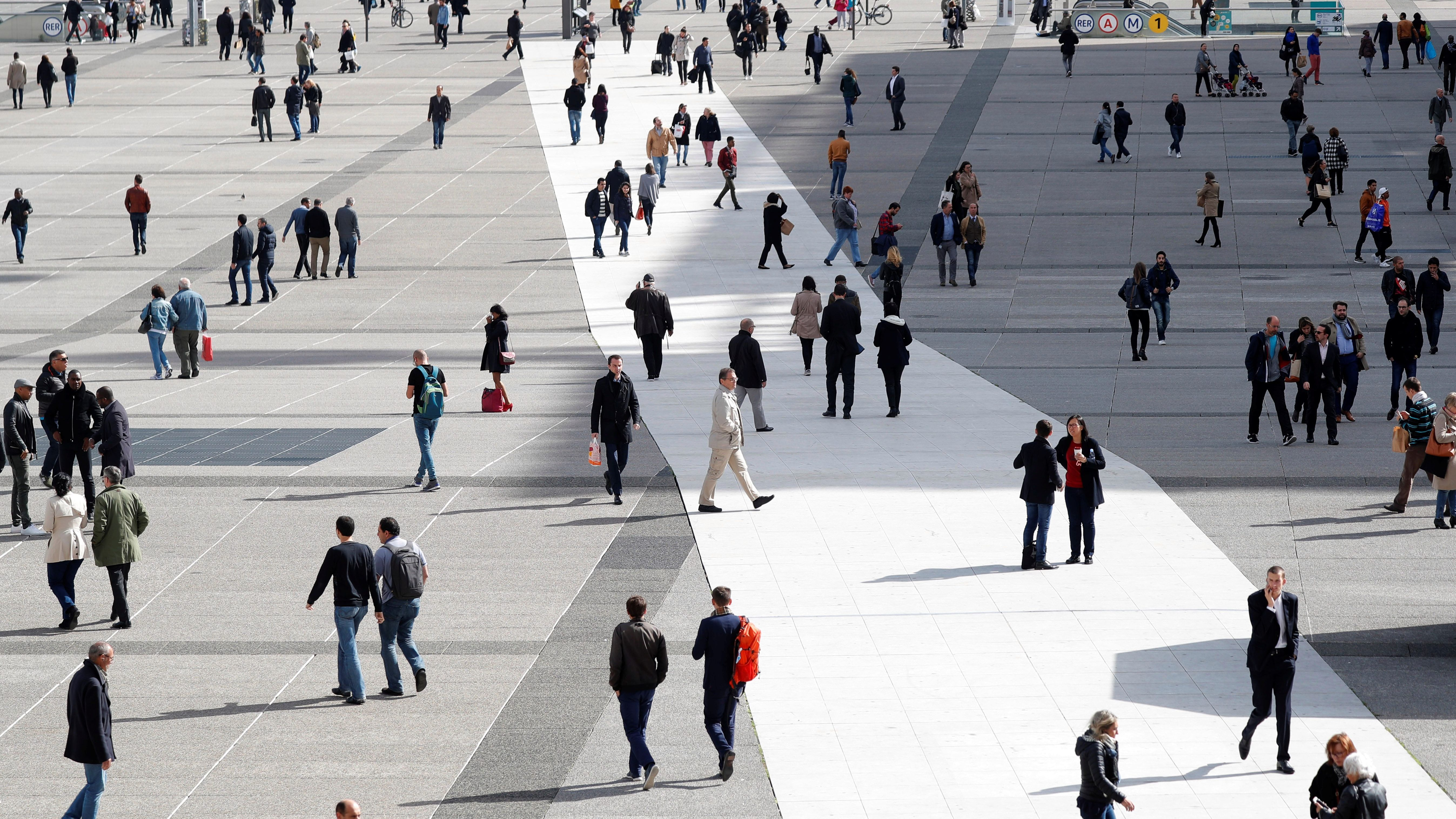 People walk on the esplanade of La Defense, in the financial and business district, west of Paris, France