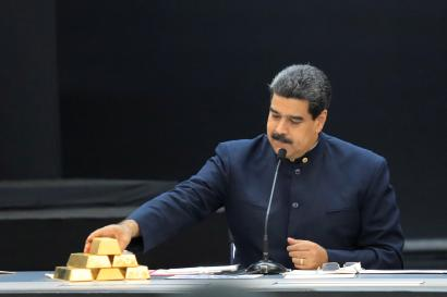 Venezuela's President Nicolas Maduro touches a gold bar as he speaks during a meeting with the ministers responsible for the economic sector at Miraflores Palace in Caracas.