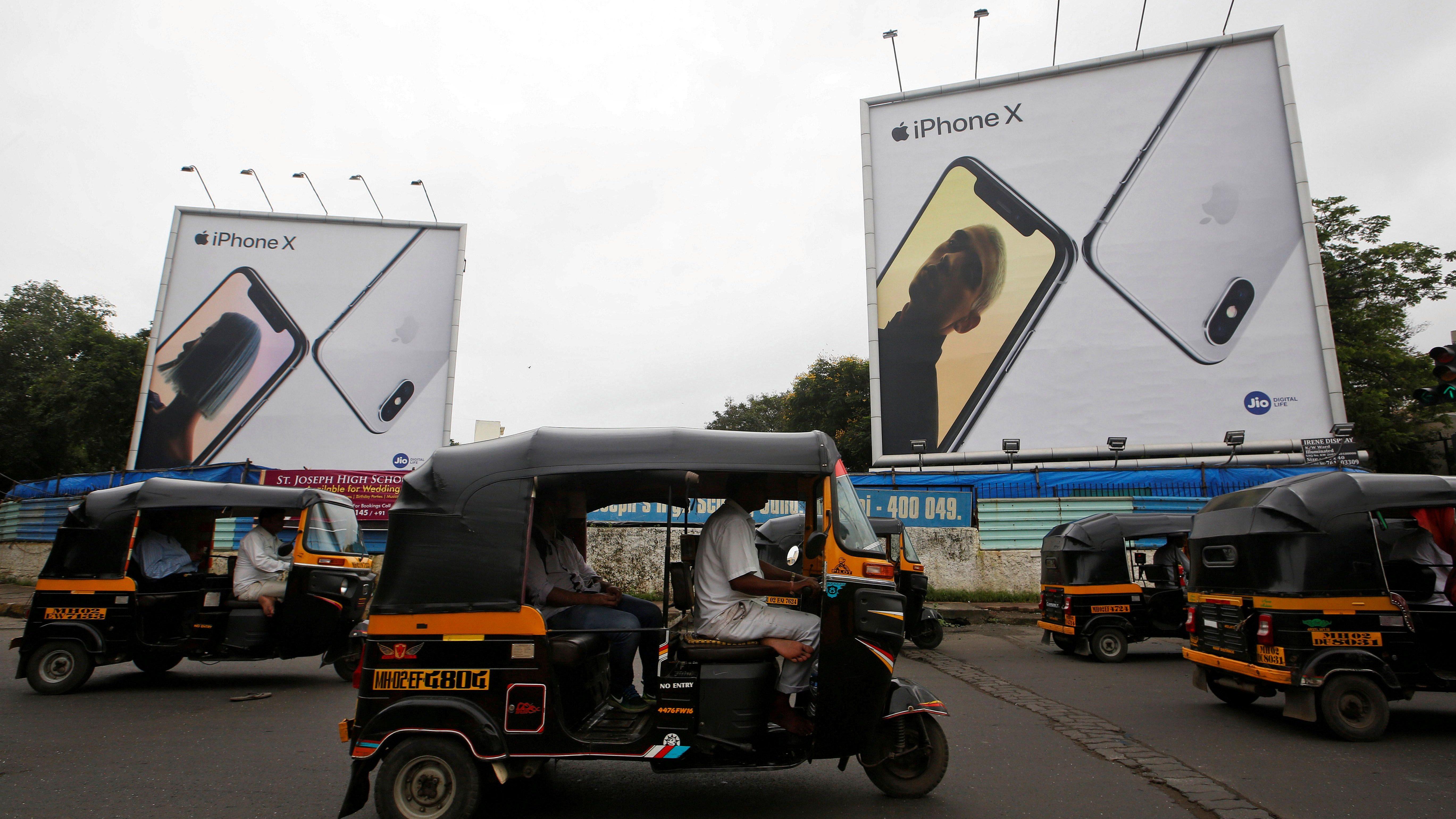 FILE PHOTO: Auto-rickshaws drive past the hoardings of Apple iPhone X mobile phones in Mumbai