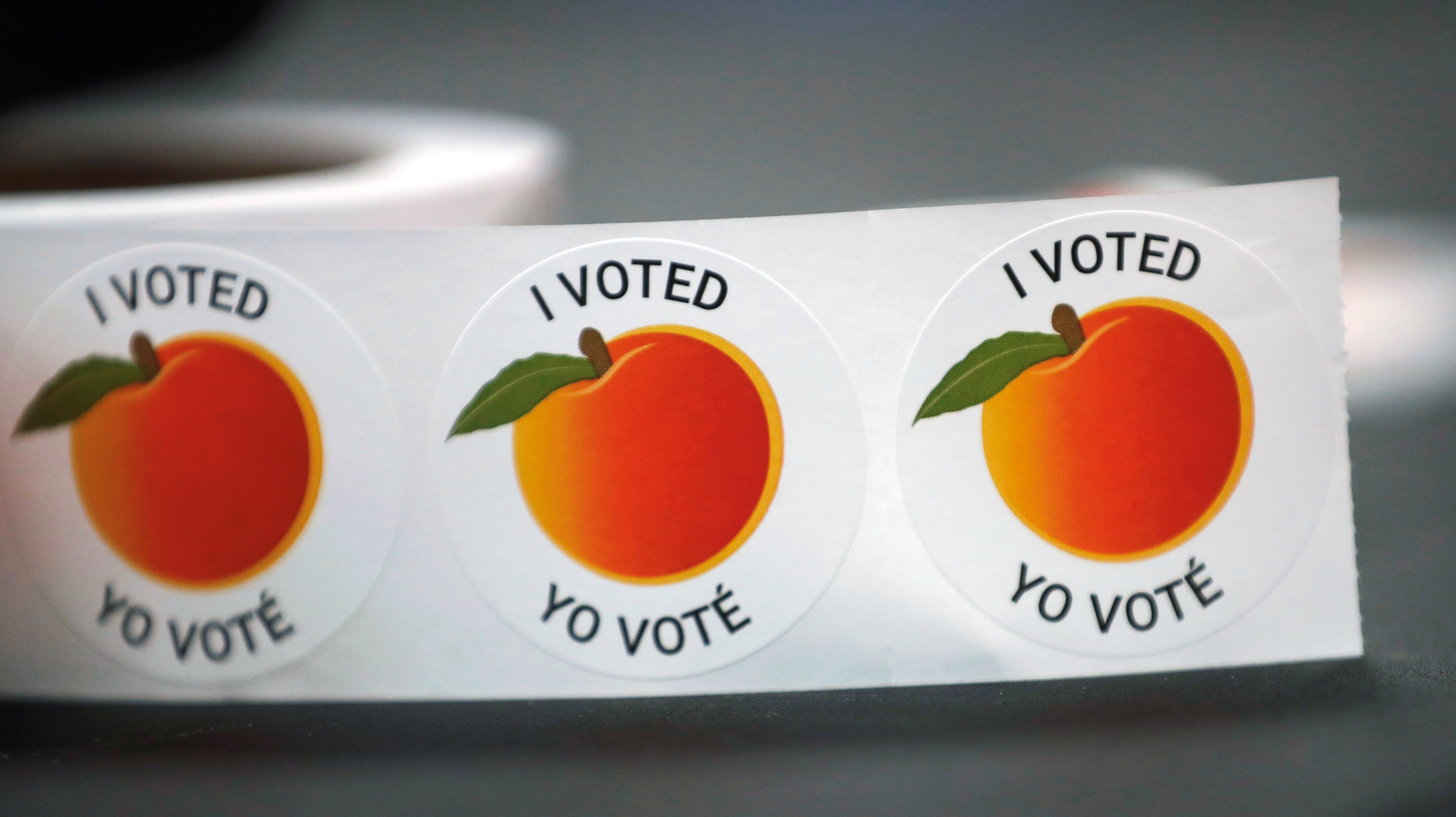 """I Voted / Yo Vote"" stickers sit on a table to be given to people after they cast their votes in the 2018 U.S. midterm election in Georgia"