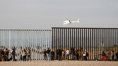 Migrants, part of a caravan of thousands trying to reach the U.S., look through the border fence between Mexico and the United States after arriving in Tijuana, Mexico,