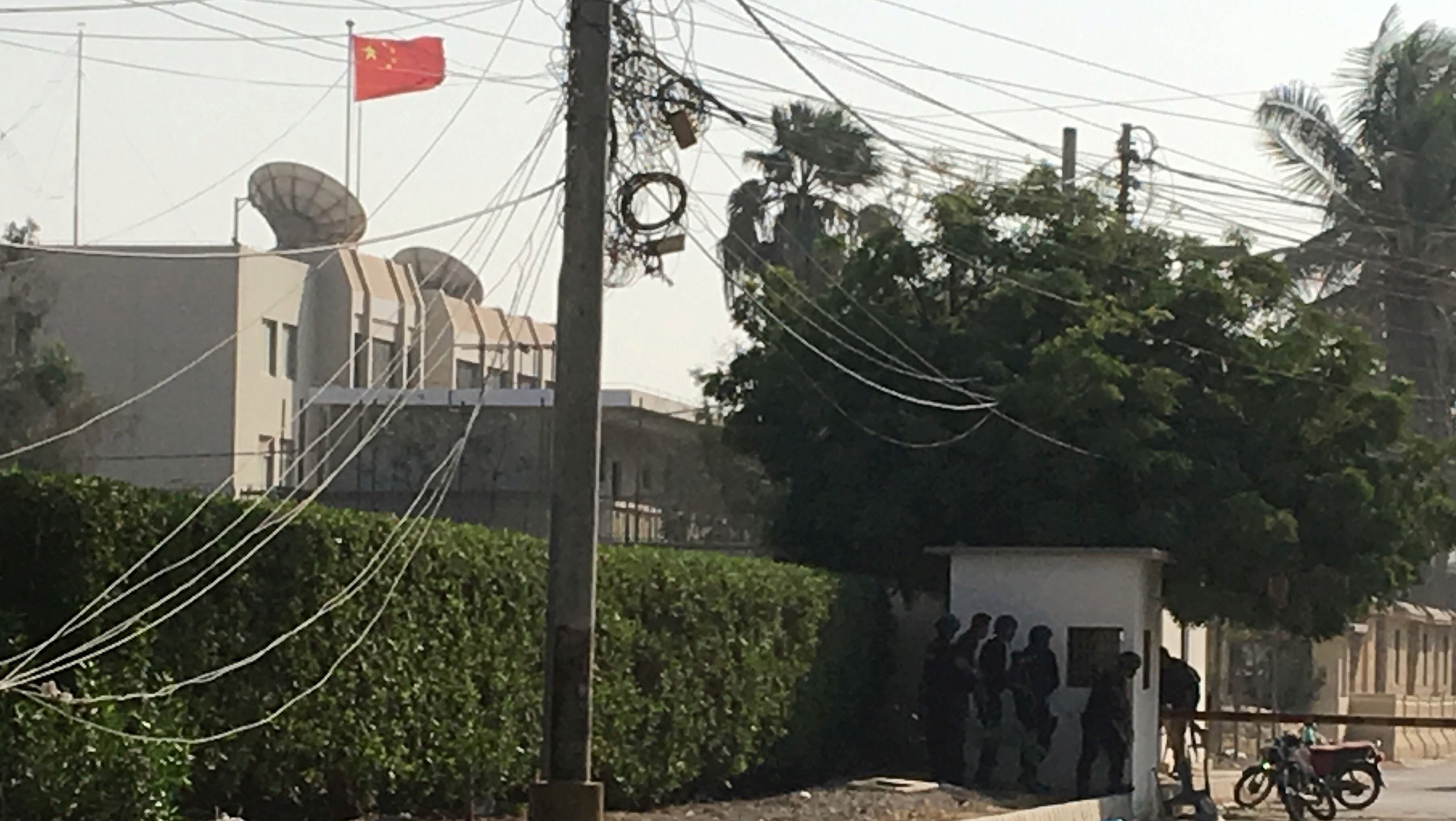 Paramilitary forces and police take cover behind a wall during an attack on the Chinese consulate in Karachi.