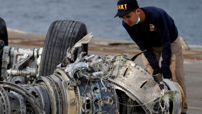 An Indonesian investigator examines a turbine engine from Lion Air flight JT610.