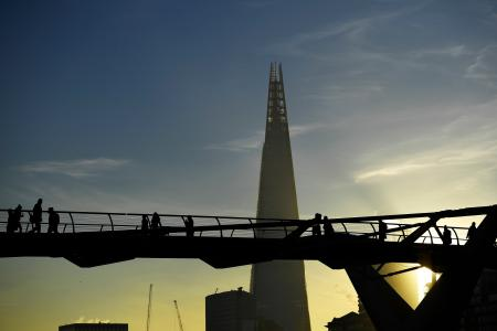 Commuters make their way across the Millennium Bridge as the sun rises over London