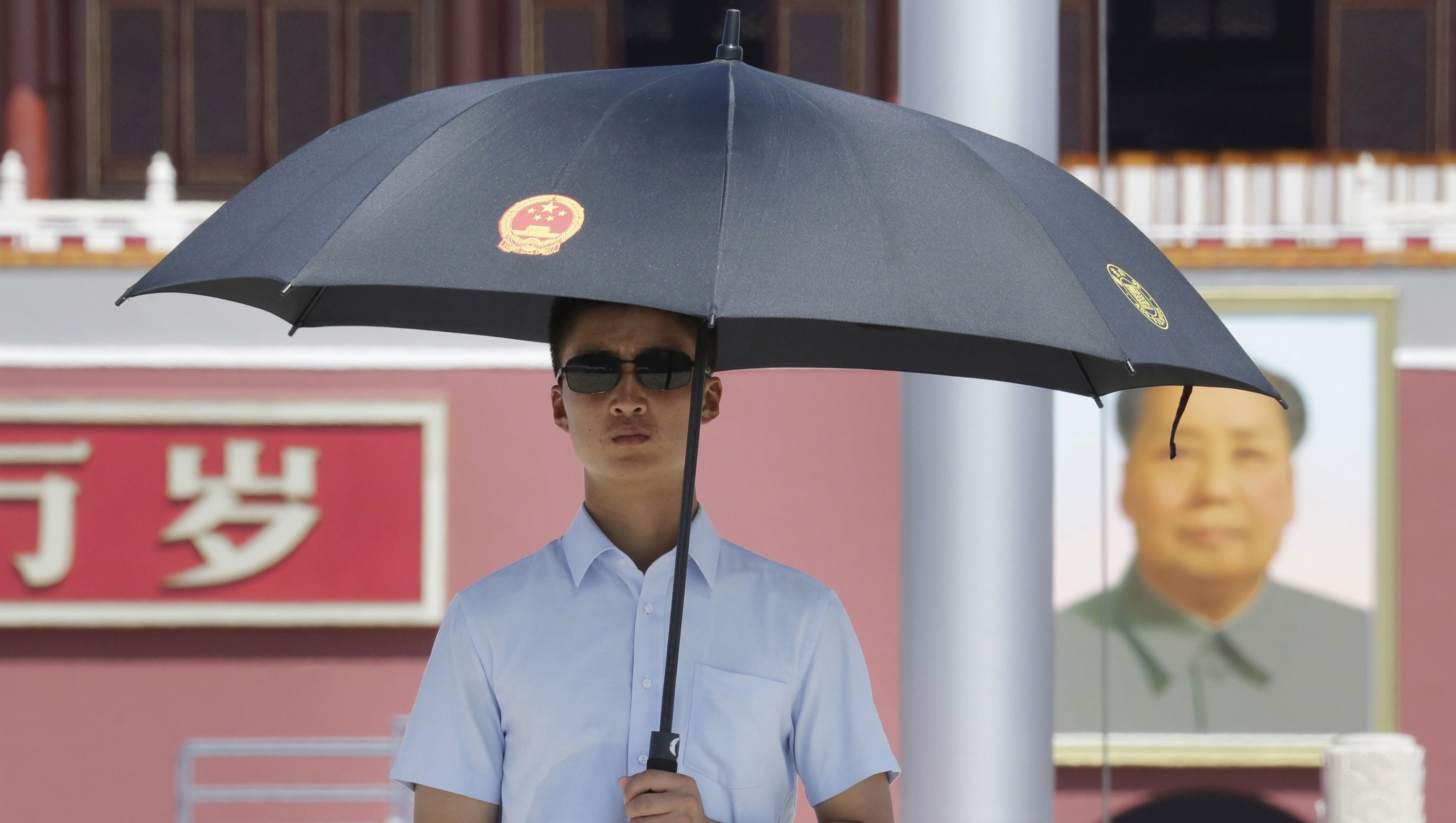 A paramilitary police officer in plain-clothes holding an umbrella keeps watch on Beijing's Tiananmen Square, August 27, 2015. Major Western leaders will not attend a military parade in China next week to mark the end of World War Two, leaving President Xi Jinping to stand with leaders and officials from Russia, Sudan, Venezuela and North Korea at his highest-profile event of 2015.