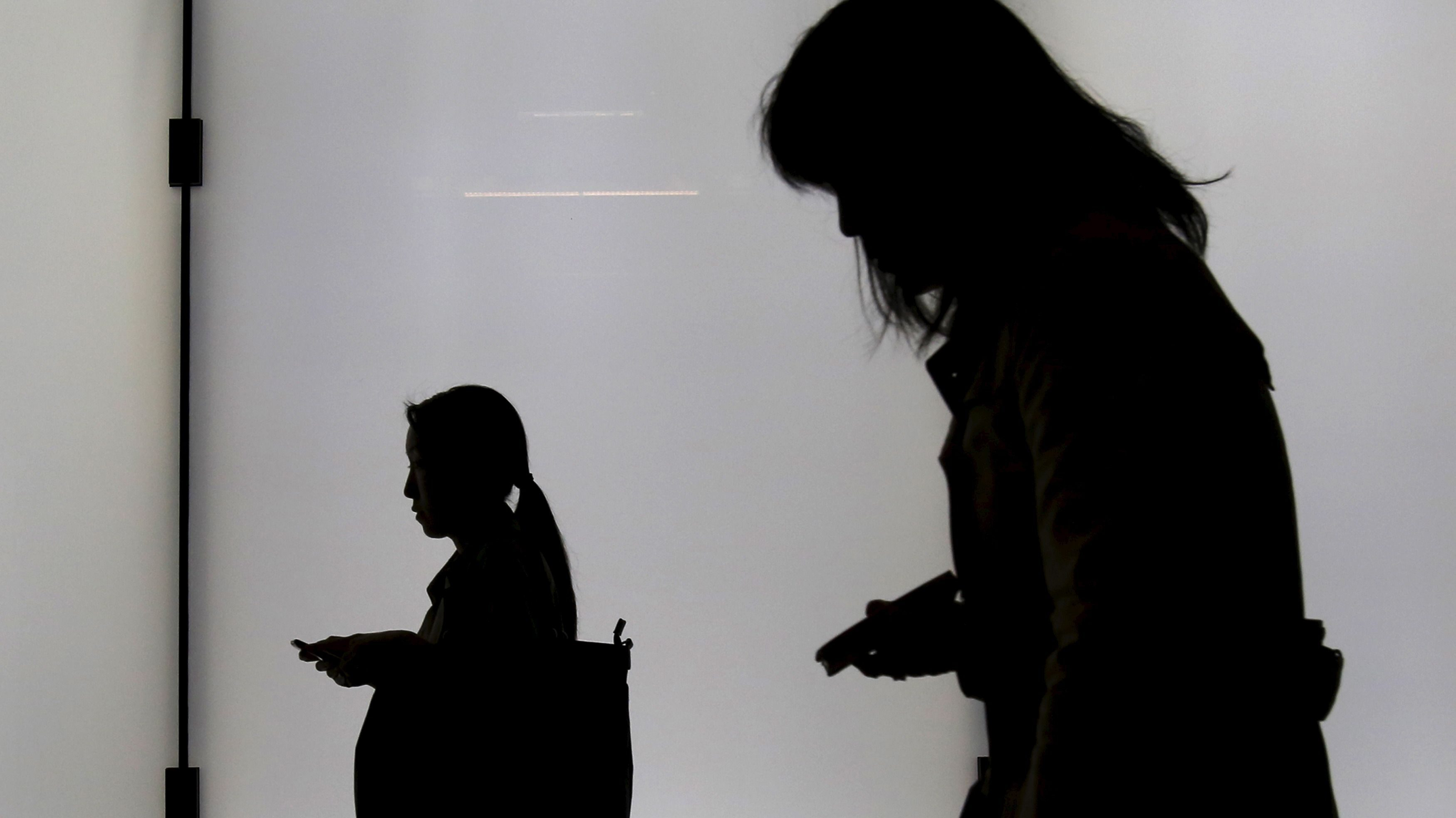 Women holding their mobile phones are silhouetted as they walk on an overpass at a business district in Tokyo, Japan, November 5, 2015. REUTERS/Yuya Shino - GF20000046605