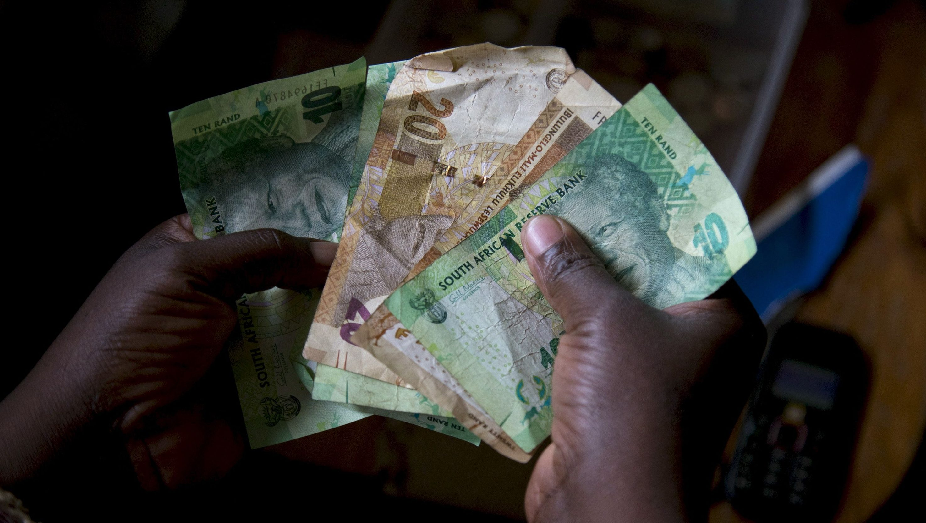 A shopkeeper counts out change above her cash box at her shop in Hillcrest, west of Durban, South Africa, January 11, 2016.