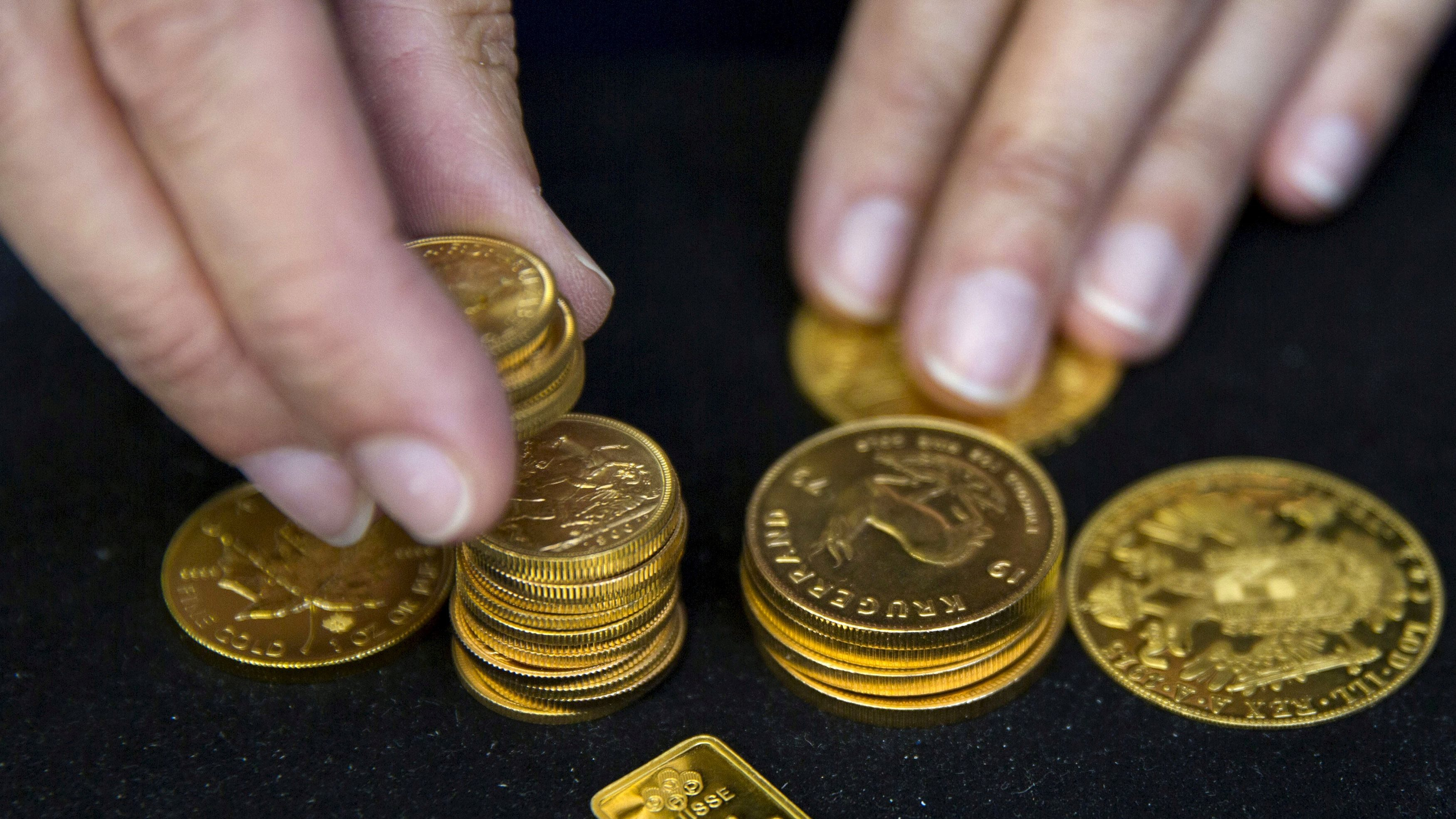 A worker places gold coins on display at Hatton Garden Metals precious metal dealers in London, Britain July 21, 2015. REUTERS/Neil Hall/File Photo - D1AETMHCTHAA