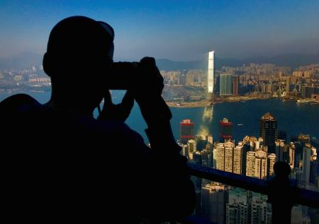 A visitor to Victoria Peak takes photographs of buildings on Hong Kong Island and Kowloon