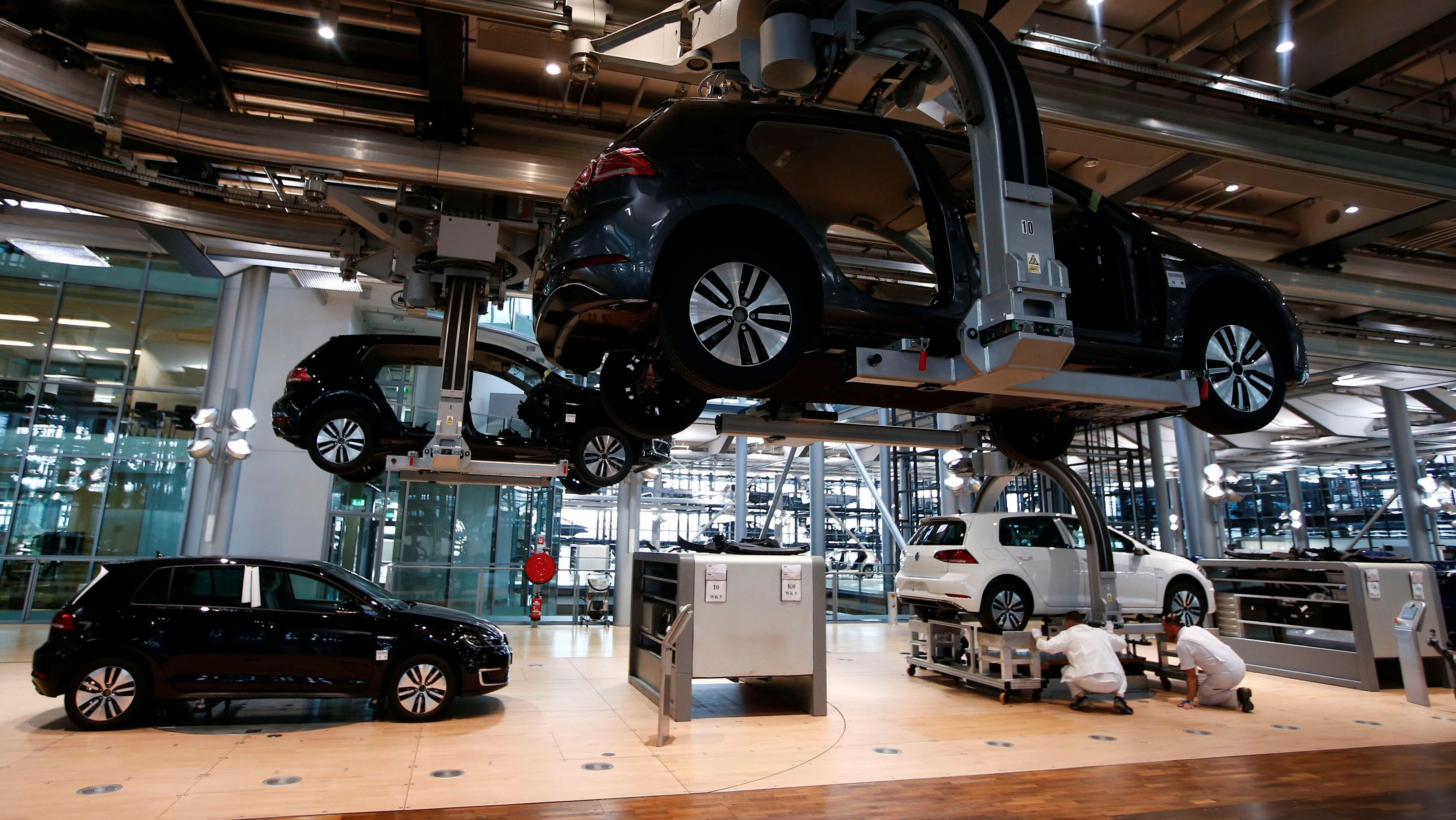 Workers assemble an e-Golf electric car at the new production line of the Transparent Factory of German carmaker Volkswagen in Dresden, Germany March 30, 2017. REUTERS/Fabrizio Bensch - RC1FB591EC90