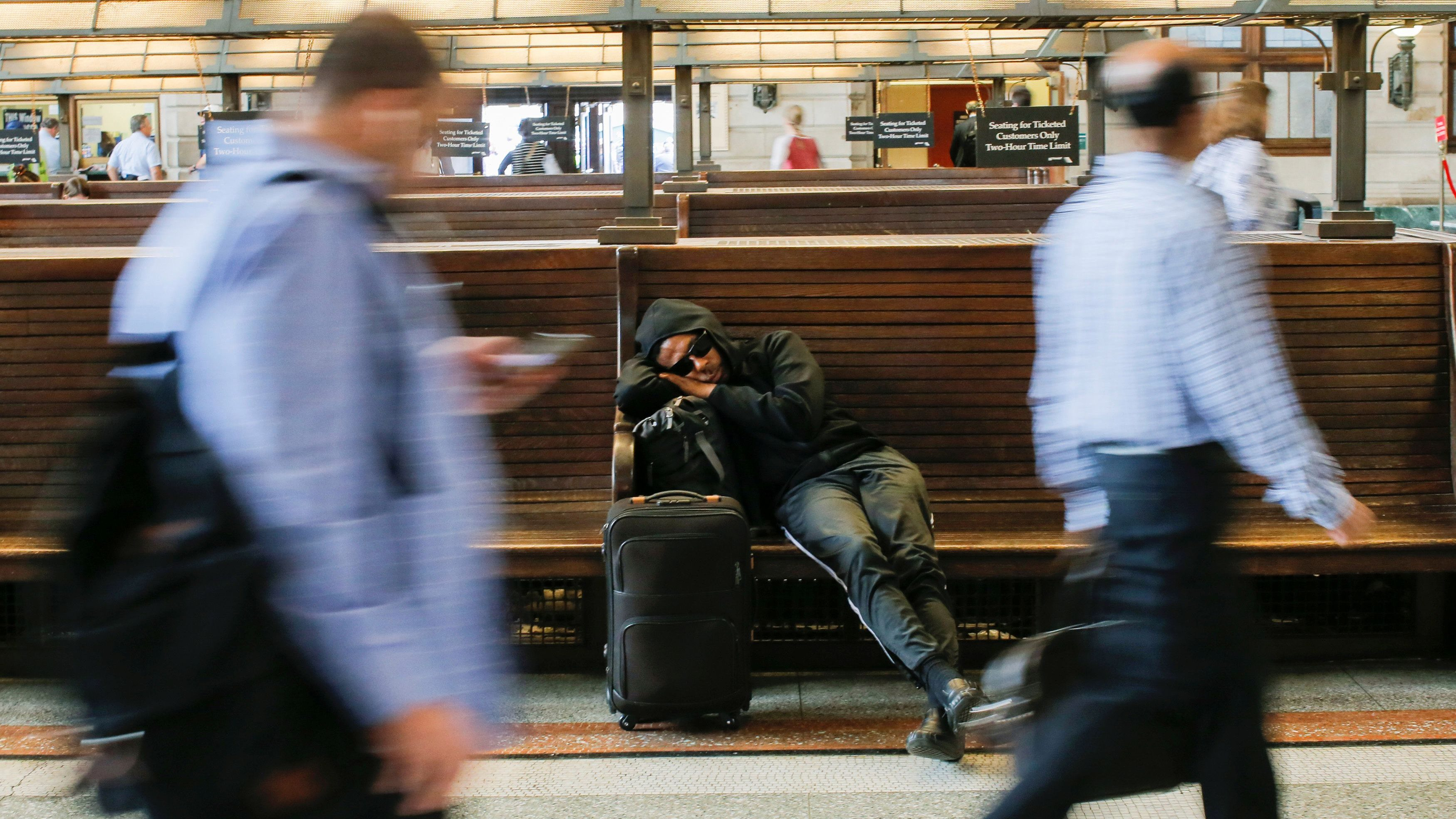 A man sleeps on a bench as people try to commute to New York at the Hoboken Terminal