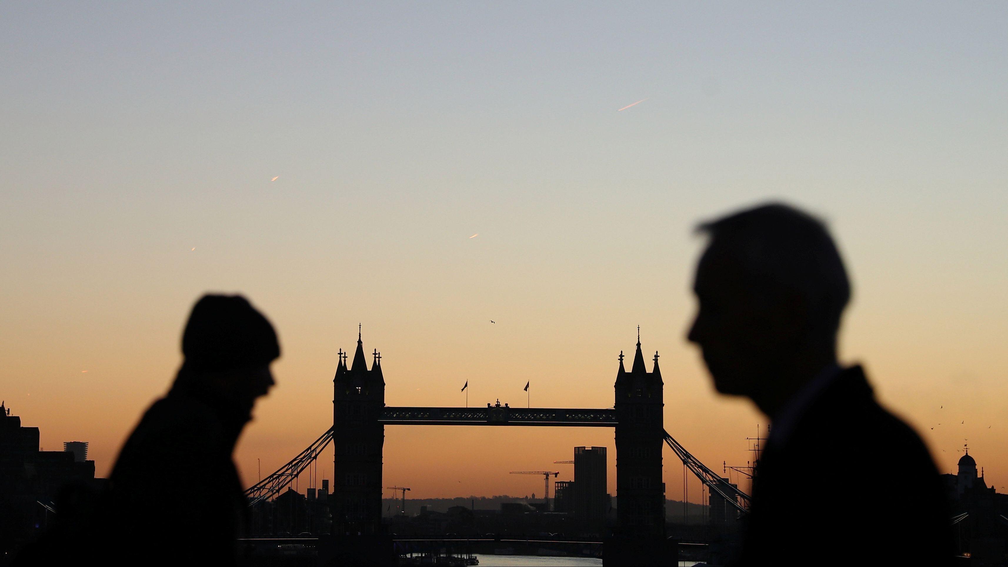 Commuters walk past Tower Bridge as the sun rises in London