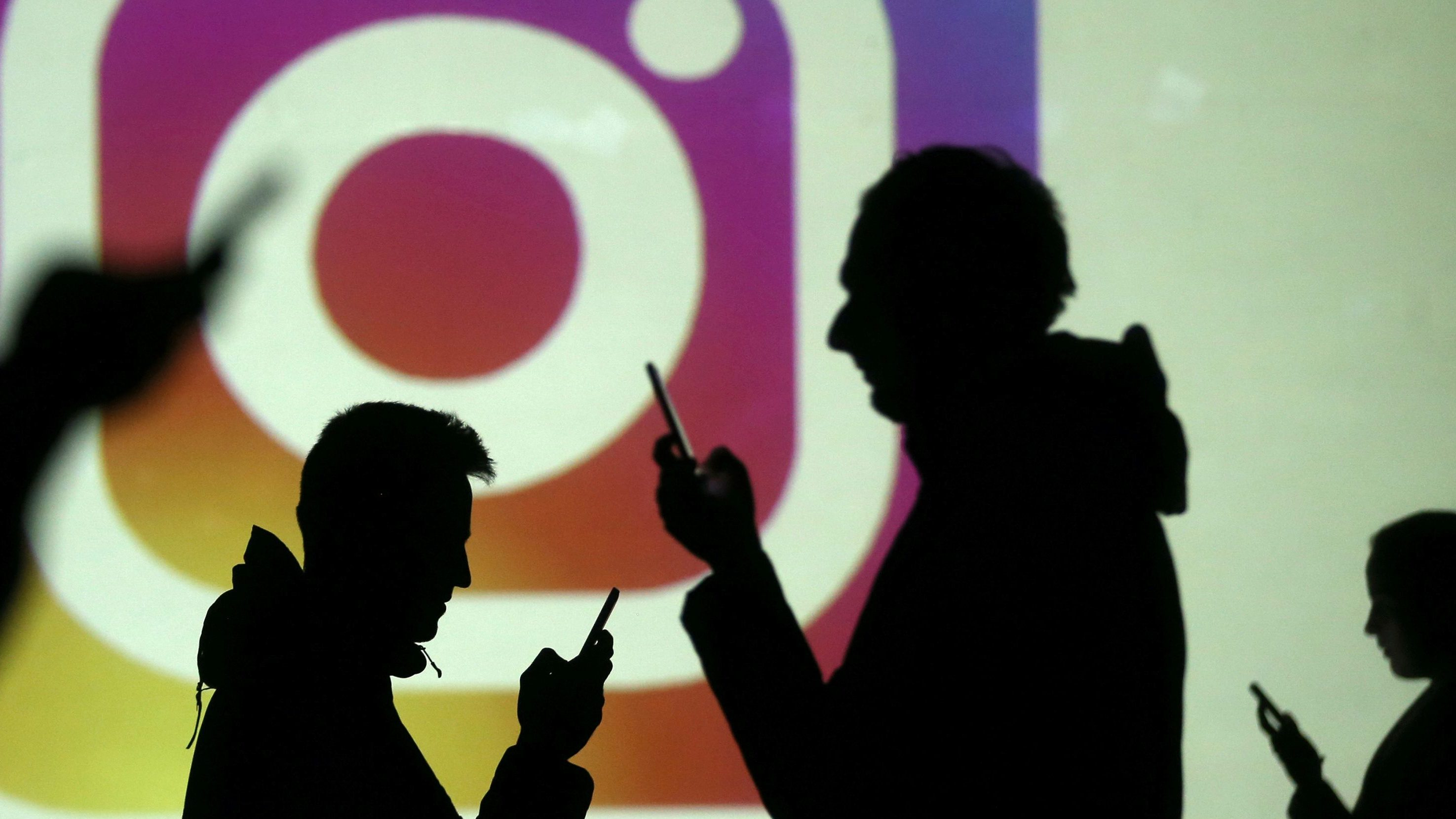 Silhouettes of mobile users are seen next to a screen projection of Instagram logo in this picture illustration taken March 28, 2018.