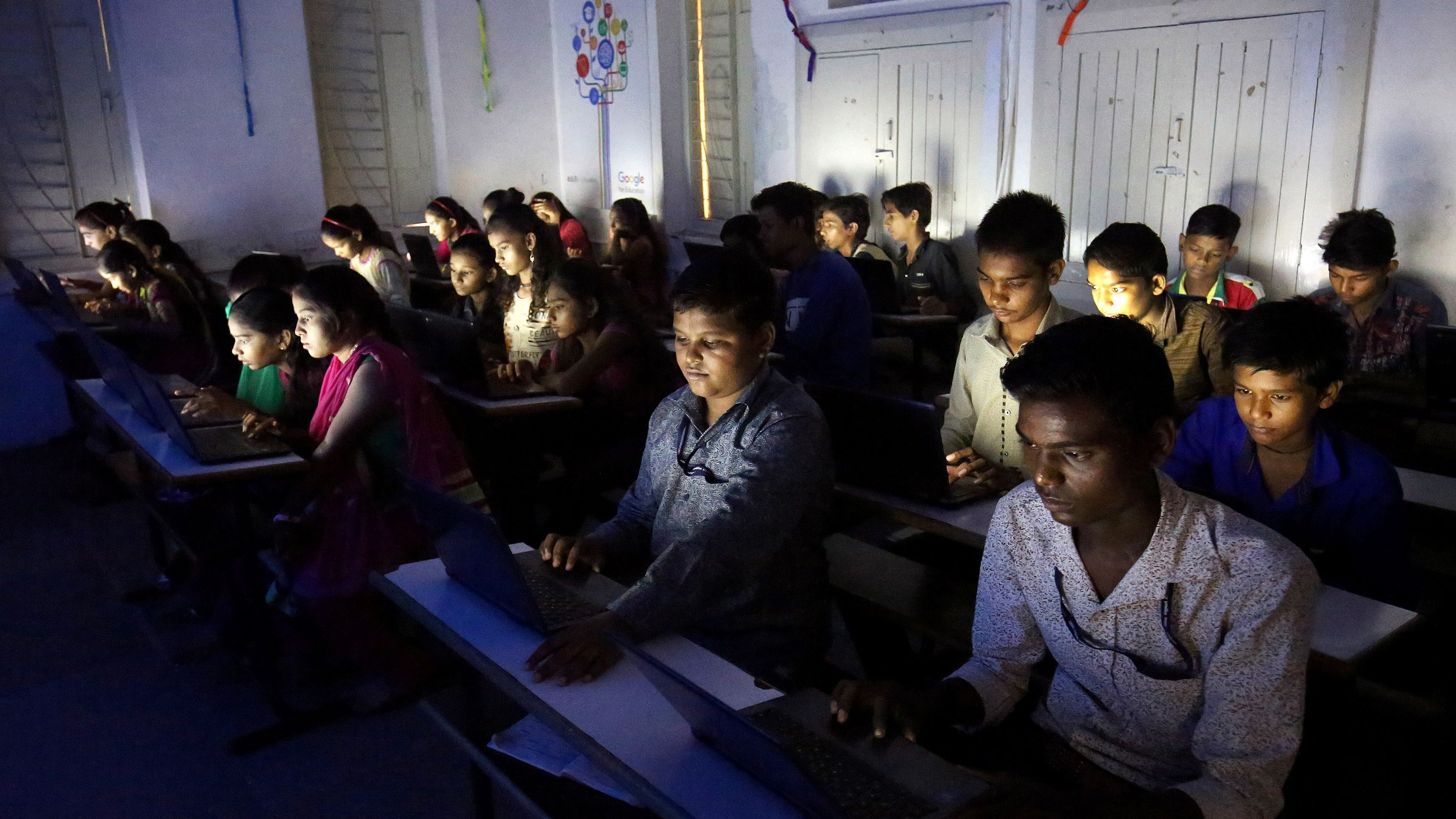 Slum students study on their laptops inside an E-classroom at a government run school in Ahmedabad