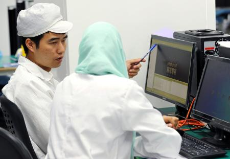 A Chinese engineer coaches a worker at the mobile phone factory in Assuit, Egypt September 30, 2018. Picture taken September 30, 2018.