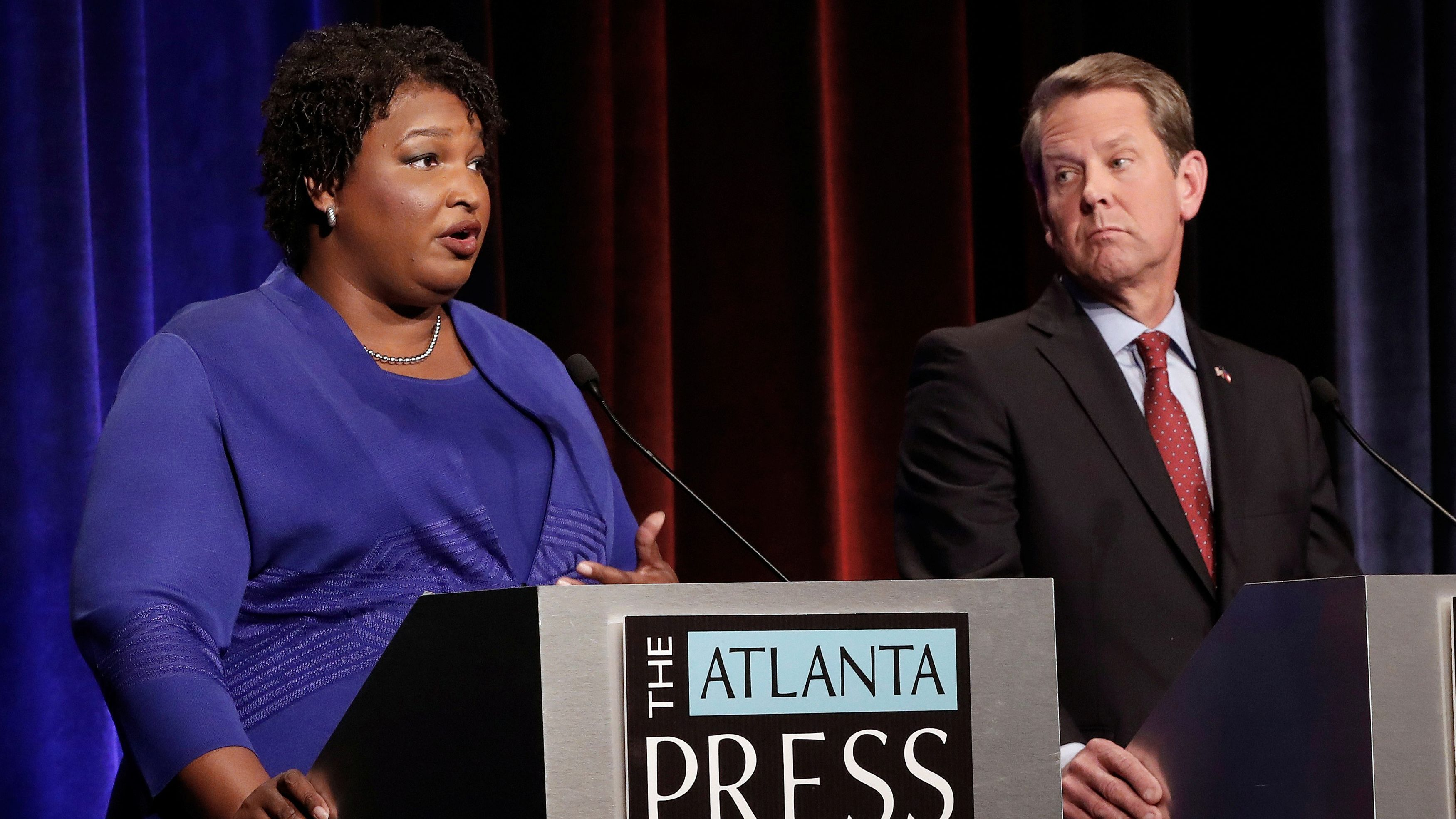 Democratic gubernatorial candidate for Georgia Stacey Abrams speaks as Republican candidate Brian Kemp looks on during a debate in Atlanta, Georgia, U.S, October 23, 2018. Picture taken on October 23, 2018. John Bazemore/Pool via REUTERS - RC1B10A44150