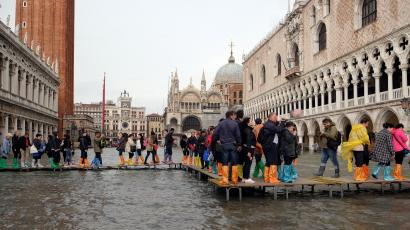 People walk on a catwalk in a flooded Saint Mark Square during a period of seasonal high water in Venice