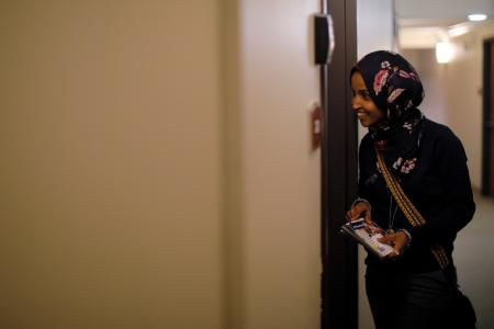 "U.S. Democratic congressional candidate Ilhan Omar ""door knocks"" to encourage voters to cast ballots in the midterm elections in Minneapolis, Minnesota, U.S., October 26, 2018. Picture taken October 26, 2018."