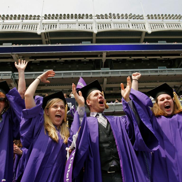 New York University graduates celebrate after having their degrees bestowed upon them.