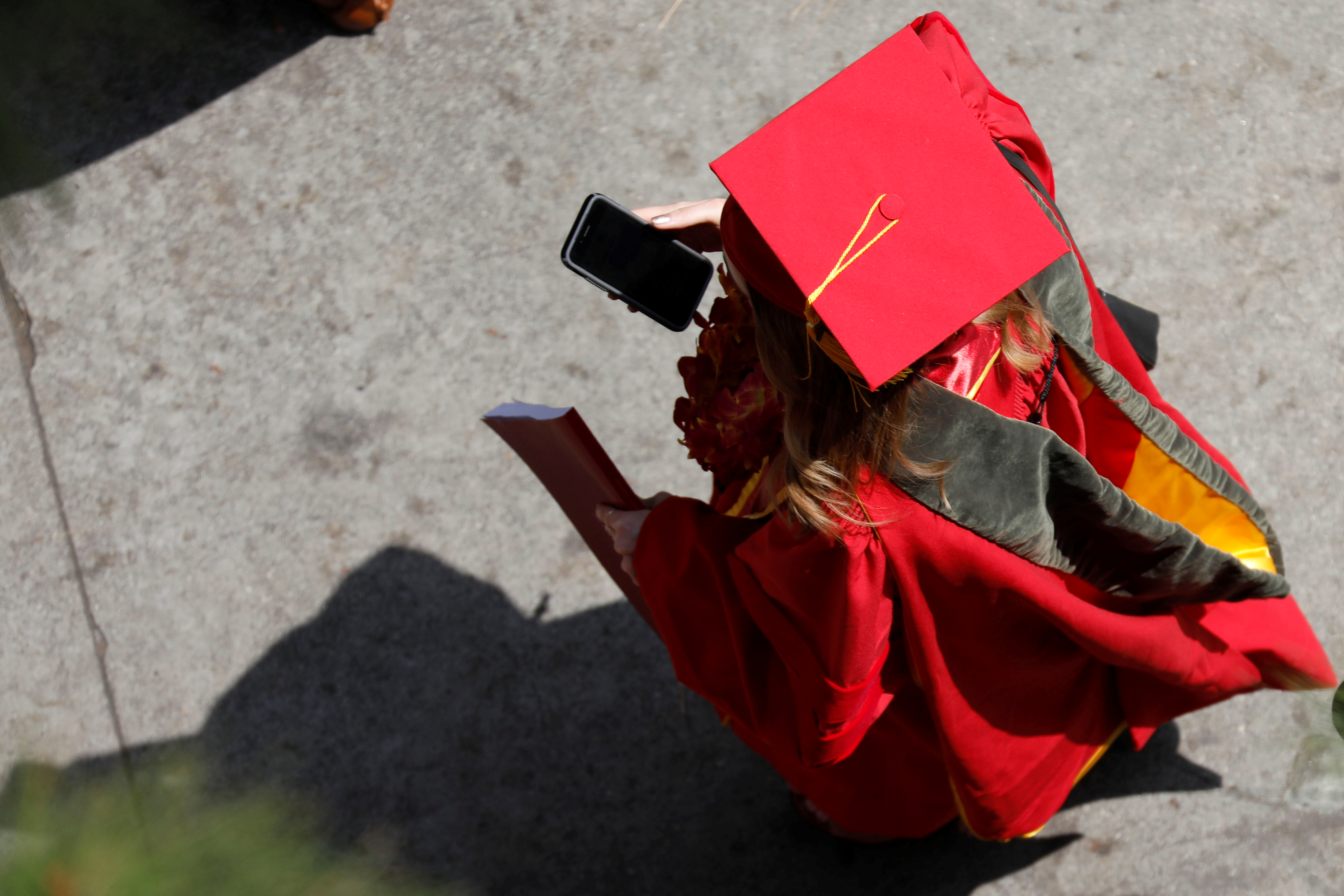 A graduate uses a cell phone after a commencement ceremony.