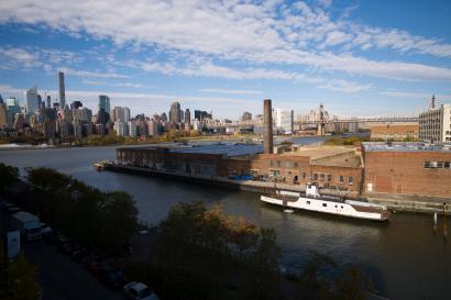 A rusting ferryboat is docked next to an aging industrial warehouse on the Anable Basin, Wednesday, Nov. 7, 2018, in the Queens borough of New York. Across the East River from midtown Manhattan, top left, Long Island City is a longtime industrial and transportation hub that has become a fast-growing neighborhood of riverfront high-rises and redeveloped warehouses, with an enduring industrial foothold and burgeoning arts and tech scenes. (AP Photo/Mark Lennihan)