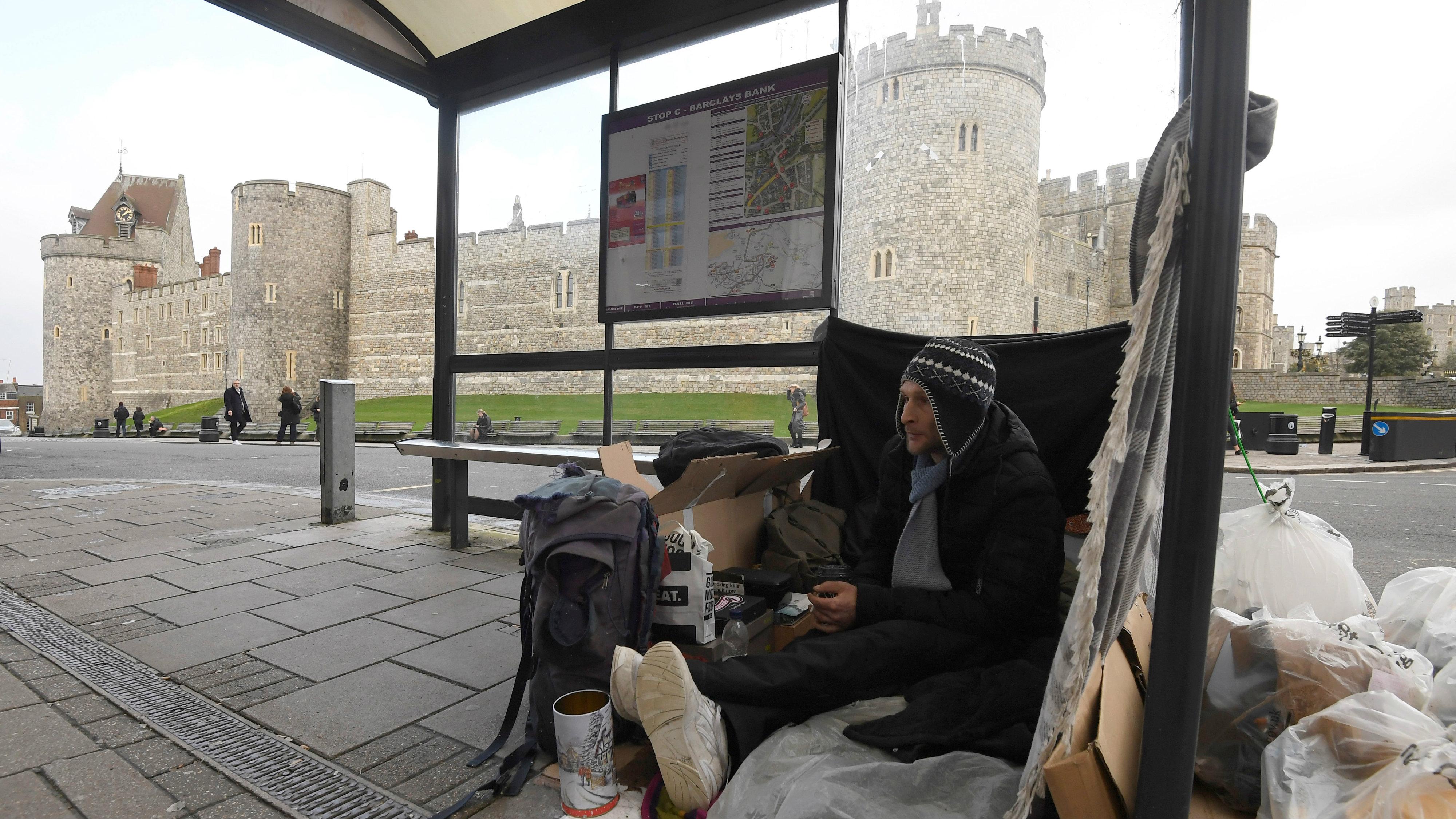 A homeless man sits under a bus shelter where he sleeps opposite Windsor Castle