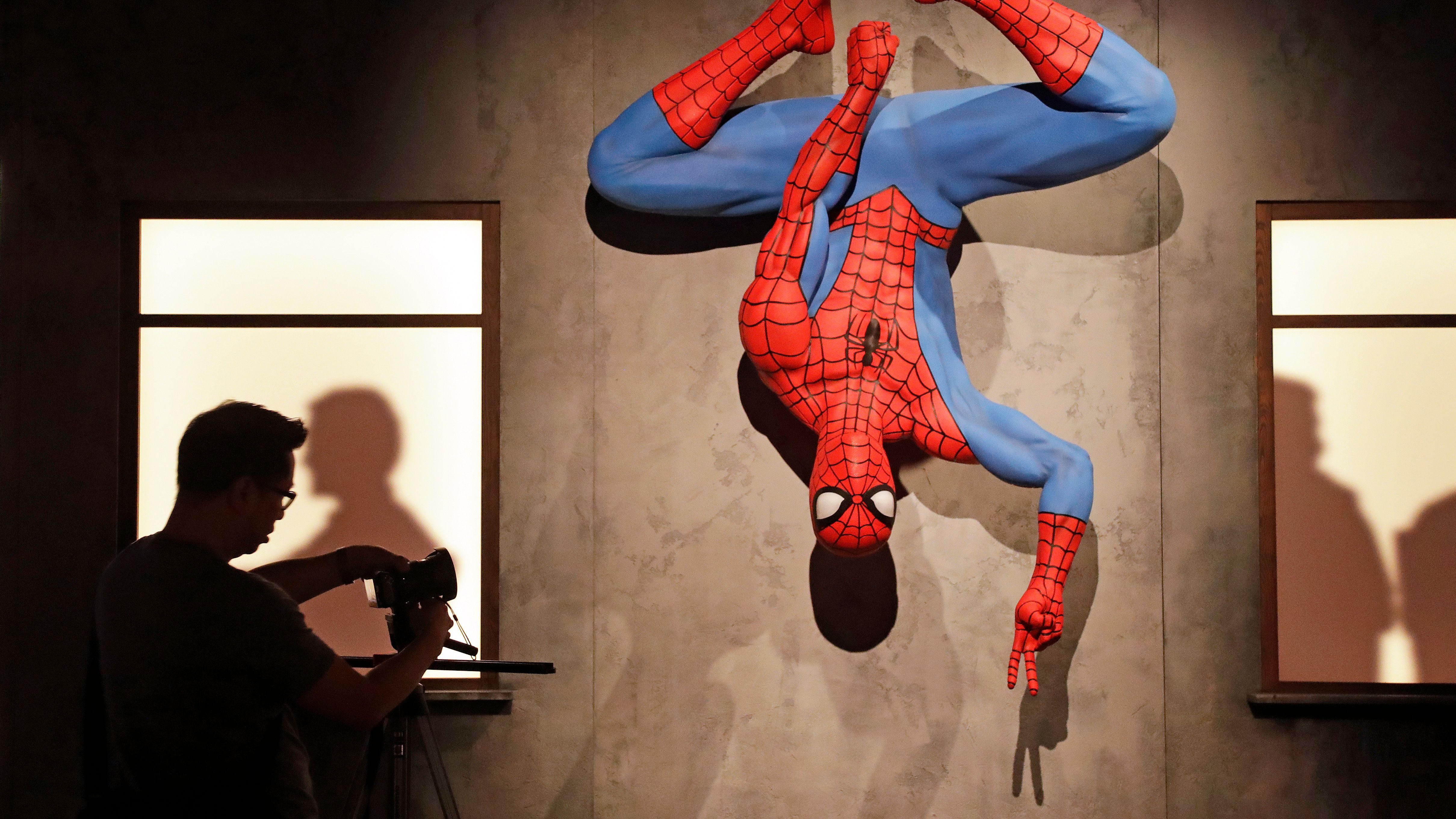 A life-size Spiderman replica hangs upside-down during a preview of the exhibit Marvel: Universe of Super Heroes at the Museum of Pop Culture (MoPOP), in Seattle.