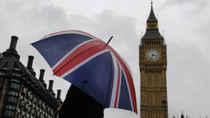 A woman holds a Union flag umbrella in front of the Big Ben clock tower