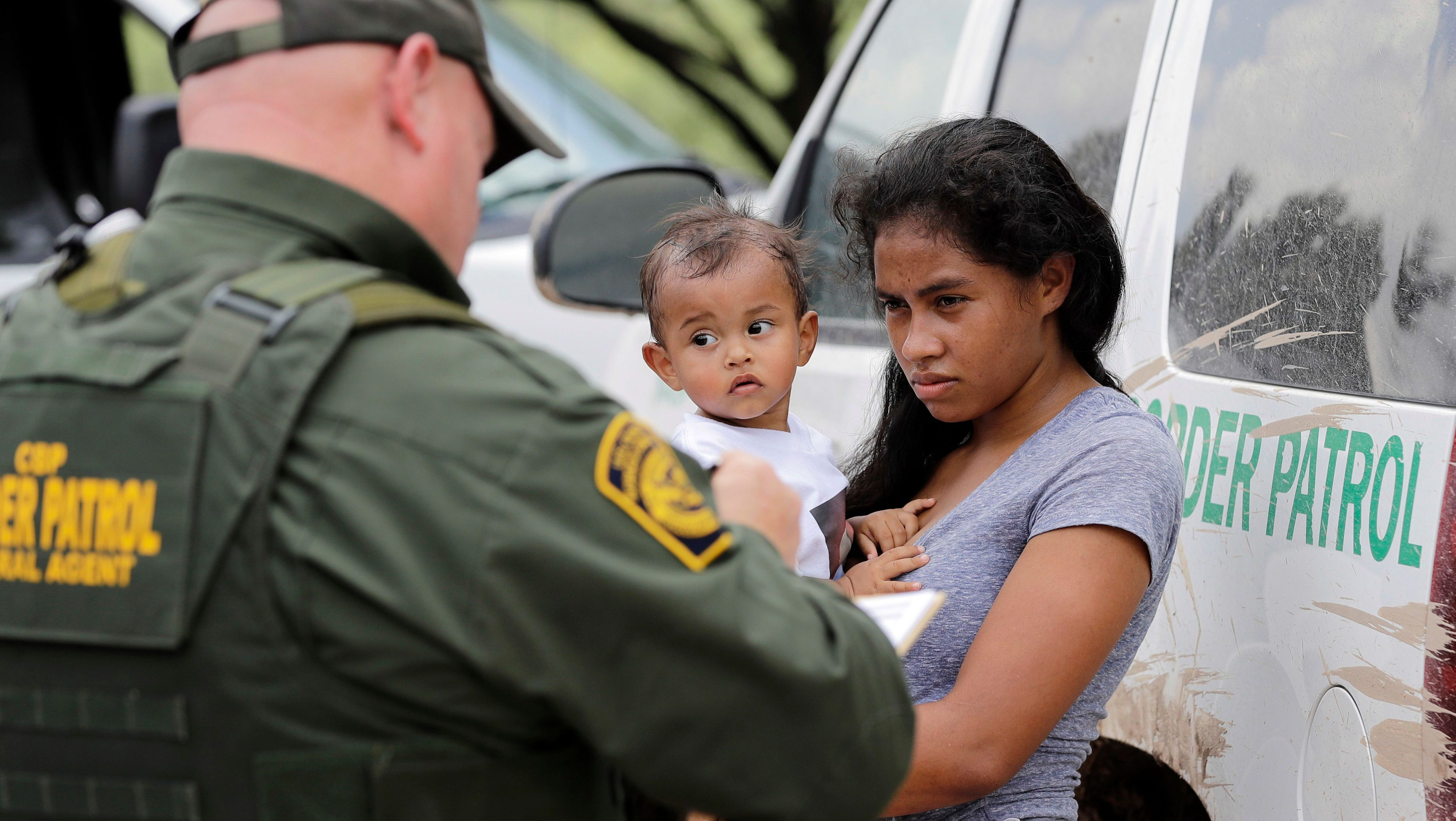 a mother migrating from Honduras holds her 1-year-old child as surrendering to U.S. Border Patrol agents after illegally crossing the border, near McAllen, Texas.